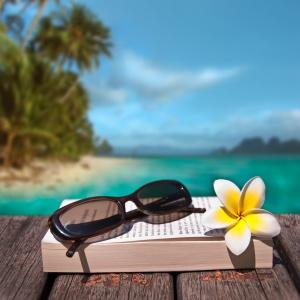 Lunettes de soleil et livre fond plage exotique